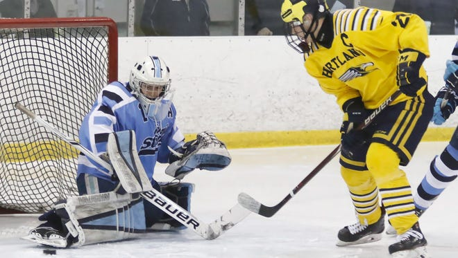 Livonia Stevenson goalie Will Tragge stops Hartland's Josh Albring for one of his 20 saves in a 3-0 victory over the Eagles in the KLAA hockey championship game on Friday, Feb. 16, 2018.