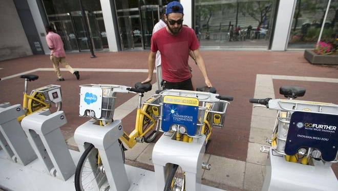 "Jake Watson, an operations technician for the Indiana Pacers Bikeshare program, docks a pair of bikes on Monument Circle, Indianapolis, on Thursday, June 11, 2015. Watson ""balances"" the bike stations and also repairs the bikes."