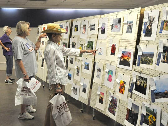Visitors look at the photography entries at the West