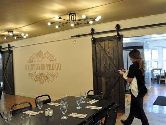Haley Jo Oates checks phone messages while prepping before food service at her restaurant Haley Jo on the Go at Under One Roof at 244 Pine St. The many updates to the space include the industrial-inspired light fixtures and sliding barn doors to the kitchen.