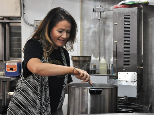 Haley Jo Oates checks on the spinach she is sauting at Haley Jo on the Go restaurant at Under One Roof at 244 Pine St.