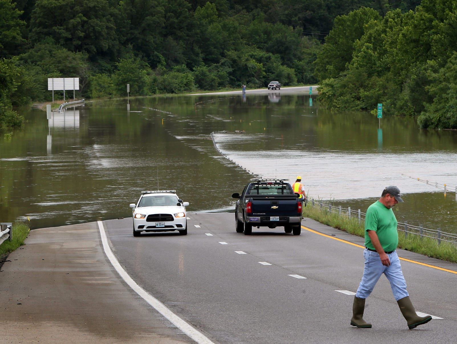 Workers and a Missouri state trooper watch as floodwater overruns Interstate 44 near Jerome, Mo.