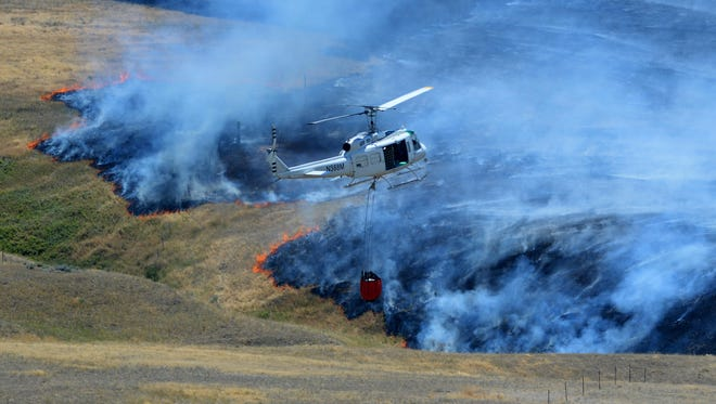 A DNRC helicopter battles a grass fire at Vinyard Road and Thunder Road in 2016.