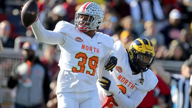 North inside linebacker Malik Harrison of Ohio State celebrates his interception with linebacker Joshua Uche of Michigan (6) at the Senior Bowl.