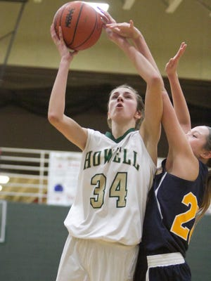 Howell's Erin Honkala shoots in the third quarter, blocked by Hartland's Lexey Tobel.