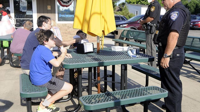 Ashland Police Chief David Marcelli, right, talks with Liam Kumpik who came to the Cones with a Cop at Eva's Treats on Claremont Avenue with his father Tom Kumpik and brother Aiden on Wednesday.