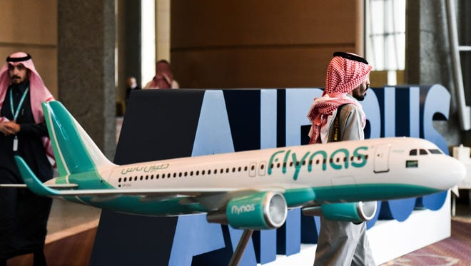 Saudis walk past a model of a Flynas plane during a ceremony for the signing of an agreement with Airbus on Jan. 16, 2017 in the capital Riyadh.