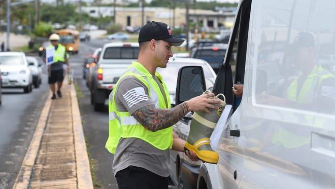 In this Jan. 26, 2017, file photo, Jose Garcia, a Guam firefighter, accepts a boot drive donation for Kusinan Kamalen Karidat at a Harmon intersection.