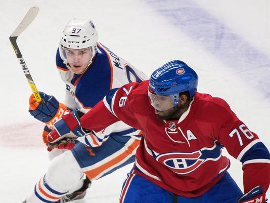 Montreal Canadiens defensemen  P.K. Subban (76) holds off Edmonton Oilers' Connor McDavid during the third period of an NHL hockey game in Montreal, Saturday, Feb. 6, 2016. (Graham Hughes /The Canadian Press via AP) MANDATORY CREDIT
