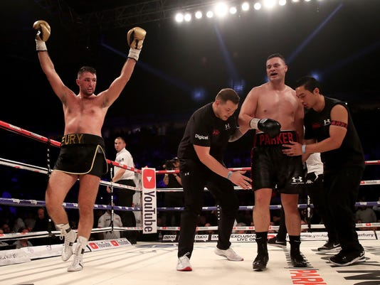 Britain's Hughie Fury, left, raises his arms as New Zealand's Joseph Parker is attended to by his staff after the WBO heavyweight title bout Saturday, Sept. 23, 2017 at Manchester Arena in Manchester, England. Joseph Parker of New Zealand retained his WBO heavyweight title by beating Hughie Fury of Britain in a majority decision on Saturday.   (Nick Potts/PA via AP)