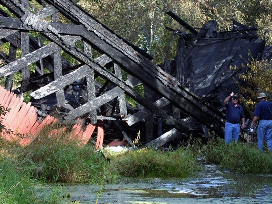 The remains of the Cedar Bridge, one of the famous covered bridges of Madison County, sits in a riverbed north of Winterset on Sept. 4, 2002, after a fire.