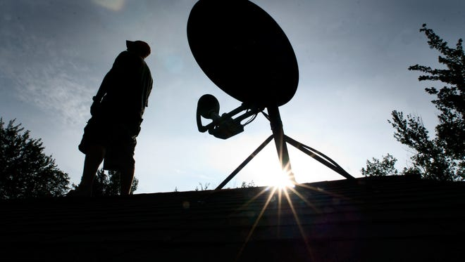 Whether in search of internet or television, many Vermonters rely on satellite signals. Here, Jeff Synder of Underhill watches the skies from the roof of his home. Photographed Aug. 4, 2010.