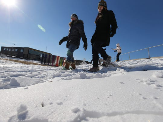 Liat Kinard of Urbandale, right, and Carol Olson of Huxley trek down a hill after they were taught how to do it in snowshoes. The women came out to try their hand at snowshoeing in the Pappajohn Sculpture Park. Des Moines Park and Recreation provided snowshoes for this stomp, led by Jill Featherstone of the Des Moines Art Center.