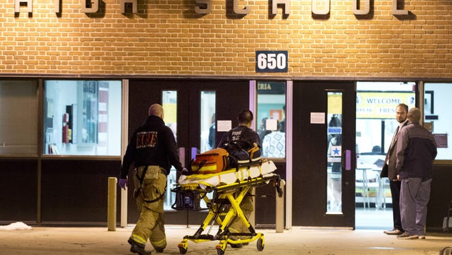 Officials enter Frederick High School, Wednesday, Feb. 4, 2015, in Frederick, Md. Police and school officials said students were shot outside the school while a basketball game was being played inside.