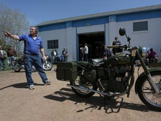 Steve Kasten points at a bidder as a 2003 Royal Enfield motorcycle is auctioned off at the S-K Service Motorcycle Swap Meet on May 10, 2014.