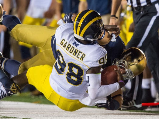 Notre Dame linebacker Kolin Hill, right, brings down Michigan quarterback Devin Gardner for a sack during the second quarter at Notre Dame Stadium. No. 15 Notre Dame won 31-0.