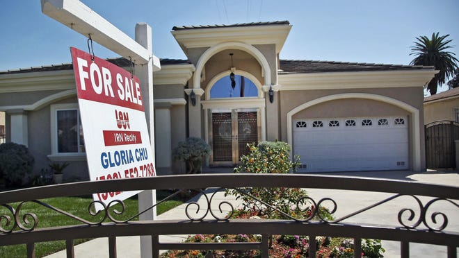 FILE: A for sale sign is posted on a home.