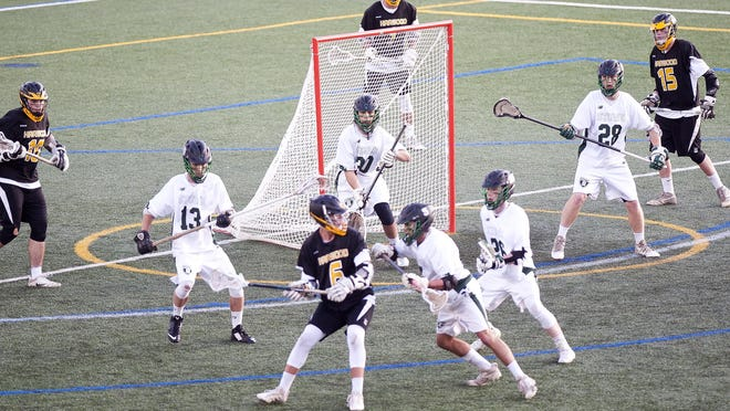 Stowe goalkeeper Bannon Wright, center, and the Raiders defense track Harwood's Connor Woolley on a possession in the third quarter of the Division II boys lacrosse championship game on Friday at Virtue Field.