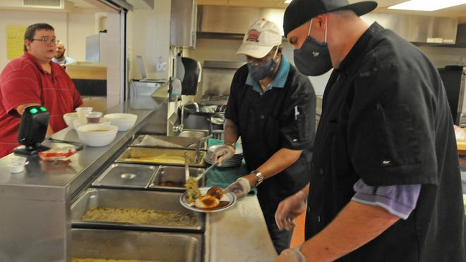 Eric Tafilowski, left, waits for his meal as Chris King and Derrick Delaughter place the food on a plate during the Salina Rescue Mission, 1716 Summers Road, lunch that is free for any community member. The Salina Rescue Mission served over 50,000 meals last year. Throughout the month of June any donations to the Salina Rescue Mission will be matched up to $50,000 by an anonymous donor.