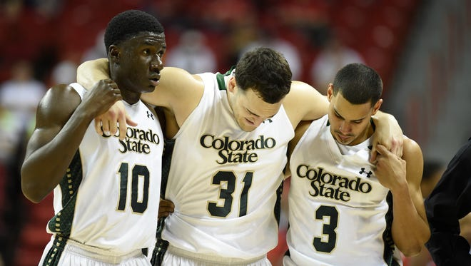 Teammates Joe De Ciman (10) and Gian Clavell (3) help injured CSU forward J.J. Avila off the floor during Thursday night's game against Fresno State at the Mountain West tournament in Las Vegas.