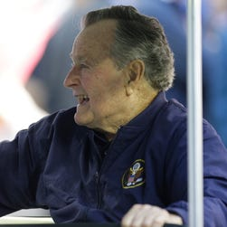 Former president George H.W. Bush smiles at the crowd before an NFL football game between the Houston Texans and the Cincinnati Bengals, Nov. 23, 2014, in Houston.