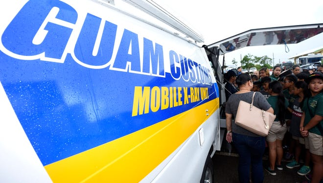 Guam Customs Public Information Officer Jessi Jon Santos-Torres describes the purpose and operation of the agency's mobile x-ray unit to Pedro C. Lujan Elementary School students during the 2018 Open House Guam Police Department static display event at the Farmer's Market in Dededo on Thursday, May 17, 2018.