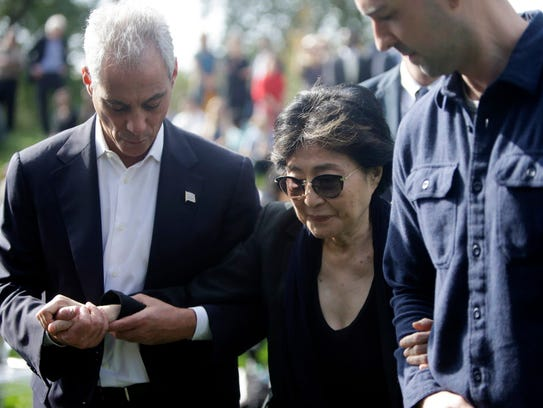 Chicago Mayor Rahm Emanuel, left, helps Yoko Ono after