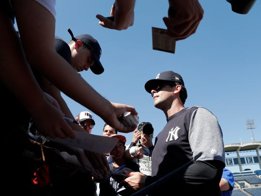 New York Yankees manager Aaron Boone signs autographs at baseball spring training camp, Sunday, Feb. 18, 2018, in Tampa, Fla. (AP Photo/Lynne Sladky)