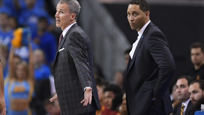 Southern California head coach Andy Enfield, left, talks to officials as assistant coach Tony Bland stands behind him during the second half of an NCAA college basketball game against UCLA, Saturday, Feb. 18, 2017, in Los Angeles. Bland along with four other coaches, were identified in court papers and are among 10 people facing federal charges in Manhattan federal court, Tuesday, Sept. 26, 2017, in a wide probe of fraud and corruption in the NCAA, authorities said. (AP Photo/Mark J. Terrill)