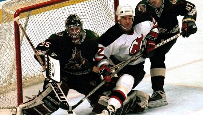 New Jersey Devils' Randy McKay, center, is checked into Phoenix Coyotes goaltender Nikolai Khabibulin, left, by Coyotes' Travis Hansen during the third period Sunday, Feb. 28, 1999, in East Rutherford, N.J.