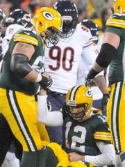 Green Bay Packers quarterback Aaron Rodgers is helped up by teammate Don Barclay after being injured getting sacked by the Chicago Bears during the first quarter of the game at Lambeau Field, Nov. 4, 2013.