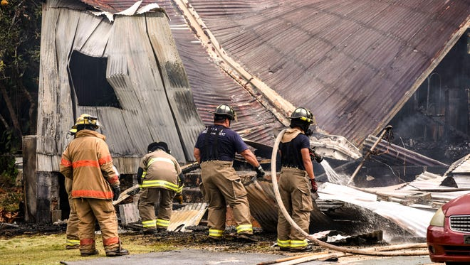 Firefighters douse hot spots of a Dededo wood-and-tin house destroyed in a fire on Friday, Jan. 26, 2018. The family pit bull Honey was leashed nearby and died, said homeowner Rose C. Perez. The house was unoccupied after the family moved to a concrete home on the same lot over a year ago, Perez said.