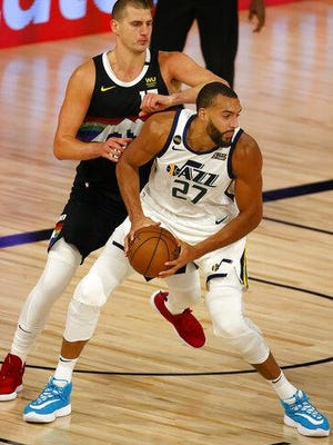 Rudy Gobert, right, of the Utah Jazz drives the ball against Denver's Nikola Jokic during the second quarter in Game 5 of the NBA playoffs Western Conference first round at The Field House at ESPN Wide World Of Sports Complex on Tuesday in Lake Buena Vista, Florida.
