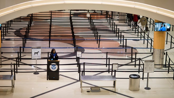 A TSA agent waits for travelers to go through security at Hartsfield-Jackson Atlanta International Airport, on Jan. 27, 2015 amid thousands of flight cancellations.