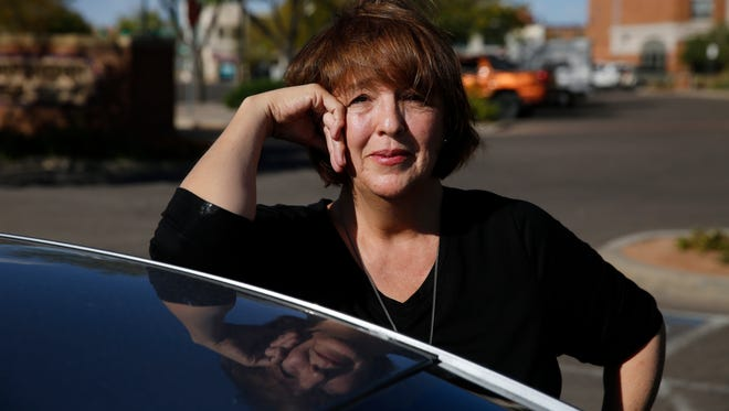 In this Oct. 4, 2016 photo, Donald Trump supporter Mary Celeste Madrid stands by her car, in Pueblo, Colo. A longtime Democrat and Obama voter who changed her registration to Republican last year over the GOP's support for gun rights and opposition to abortion, Madrid says she's also had to endure family battles over her support for Trump.