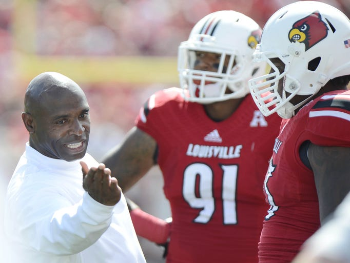 Sep 21, 2013; Louisville, KY, USA; Louisville Cardinals head coach Charlie Strong talks with defensive tackle Roy Philon (93) during the second quarter of play against the FIU Golden Panthers at Papa John's Cardinal Stadium. Mandatory Credit: Jamie Rhodes-USA TODAY Sports