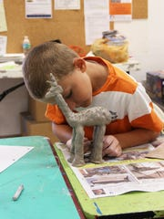 A student creates a sculpture during the Clay Holiday Fun Camp class.