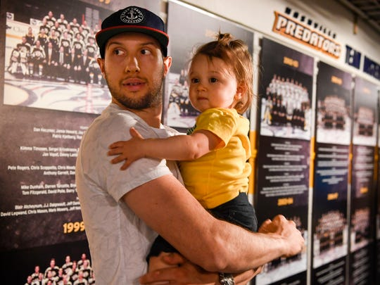Nick Bonino holds his daughter Maisie as he looks back towards the media after the announcement that he is joining the Nashville Predators at the Bridgestone Arena in Nashville, Tenn., Thursday, July 6, 2017.