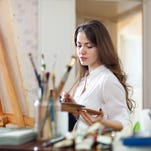 Long-haired woman  paints on canvas in workshop interior.