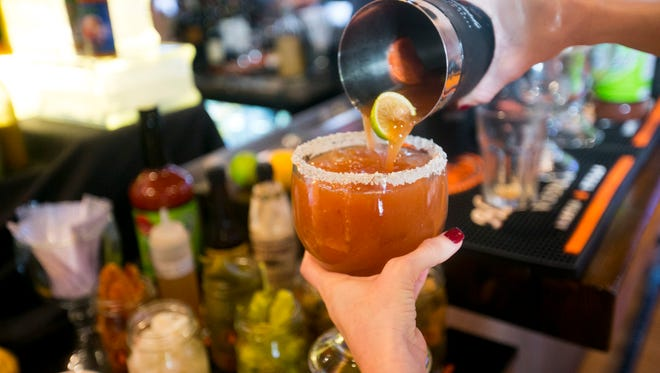 Bartender Laura McCarthy pours a Bloody Mary from a shaker at the Arcadia Tavern in Phoenix as seen on Saturday, December 13, 2014.at the Arcadia Tavern in Phoenix as seen on Saturday, December 13, 2014.