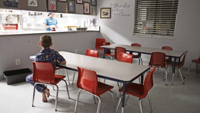 An 8-year-old boy sits in the kitchen waiting a snack at Child Crisis Arizona  in January.