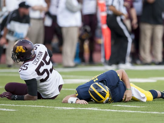 Michigan quarterback Shane Morris lays on the ground after being tackled by Minnesota defensive lineman Theiren Cockran in the fourth quarter on Saturday.