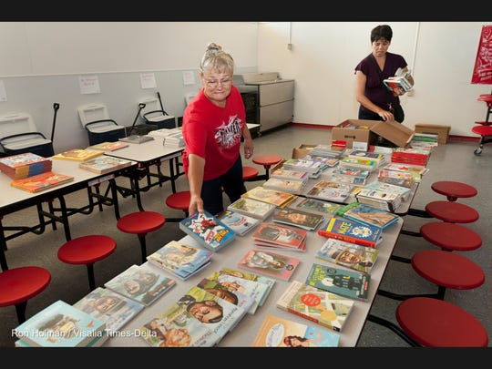 Food Service Director Paty Brehm, left, and Sarah Ramirez spread out books in preparation for nearly 300 students at Traver Elementary that were given new backpacks and books on Thursday, August 21, 2014. Visalia County Center Rotary Club filled backpacks provided by Tulare County Federal Credit Union with non-perishable items like cereal, peanut butter, milk, juice and spaghetti from FoodLink. The students also selected books provided by a grant from First 5 and Visalia County Center Rotary Club. The backpacks were printed by California Apparel.