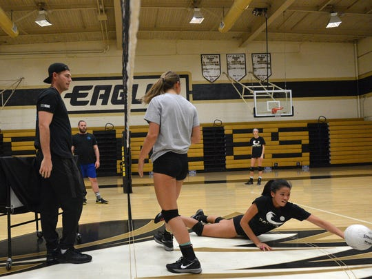 Head coach Adam Quinn (from front left), works with Natalie Litvak and Lauren Herrera during an Oak Park girls volleyball team practice Wednesday.   The team has clinched the Coastal Canyon League title and is getting ready for the playoffs.