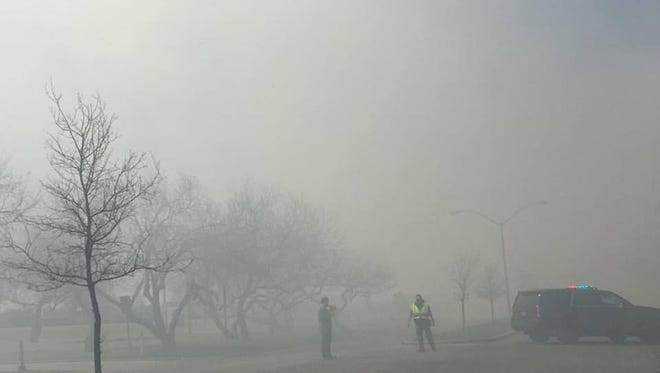 Police in Kingsville block are blocking roads while firefighters extinguish a grass fire Sunday afternoon.
