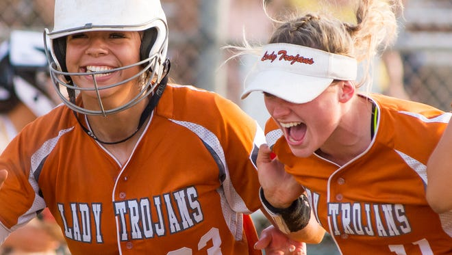 Beeville's Saleen Flores (left) and Tierra Moore celebrate outside the dugout after Flores scored the game-tying run in the sixth inning of the Trojans' win over Rio Hondo in Game 2 of their Region IV championship series Saturday at the Cabaniss Softball Field. Beeville went on to win 4-3 in eight innings to sweep the series and earn a berth at the state tournament for the first time since 1997.