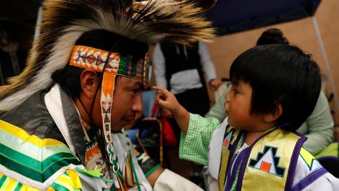 Alex Willie helps his son Ayden Willie get dressed last year before participating in a dance at the Totah Festival at the Farmington Civic Center. The event returns this weekend.