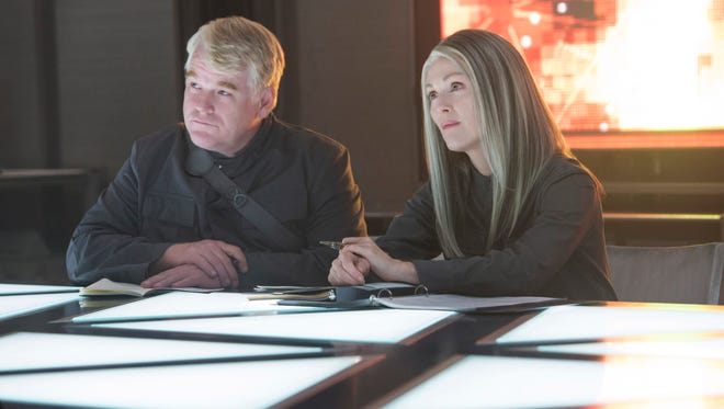 """This photo released by Lionsgate shows, Philip Seymour Hoffman, left, as Plutarch Heavensbee and Julianne Moore as President Coin in a scene from the film, """"The Hunger Games: Mockingjay - Part 1."""" The movie releases on Nov. 21."""
