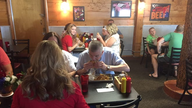 """Senate candidate Matt Rosendale dives into the """"Commander In Beef"""" burger prior to President Trump's visit Thursday at the Roadhouse Diner."""