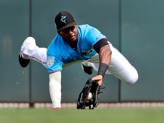 Miami Marlins center fielder Lewis Brinson dives to catch a fly ball by Washington Nationals' Adam Eaton for an out during the third inning of an exhibition spring training baseball game Friday, March 1, 2019, in Jupiter, Fla. (AP Photo/Jeff Roberson)